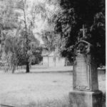 Grabstein, im Hintergrund kann man die alte Trauerhalle erkennen